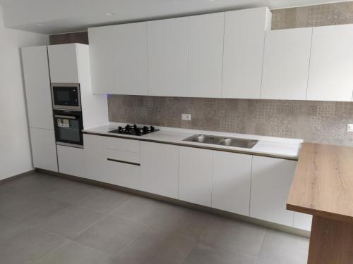 cucina bianca lineare con top in quarzo e penisola 10