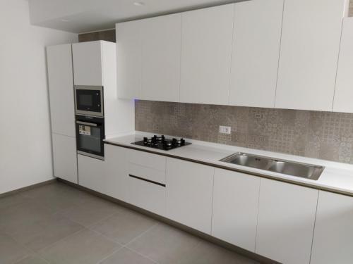 cucina bianca lineare con top in quarzo e penisola 6