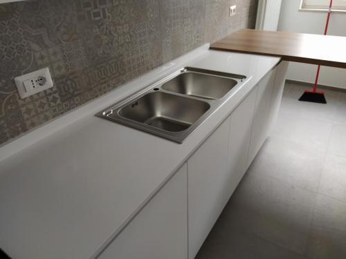 cucina bianca lineare con top in quarzo e penisola 8