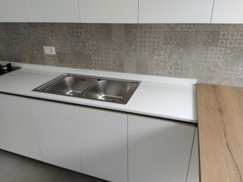 cucina bianca lineare con top in quarzo e penisola 9